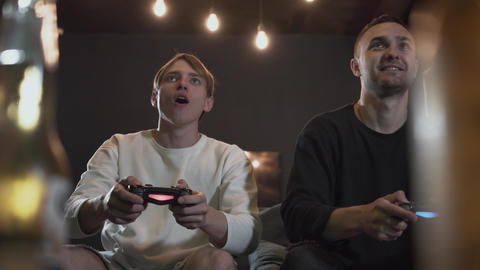 Handsome young friends having fun on evening playing video games drinking beer Footage