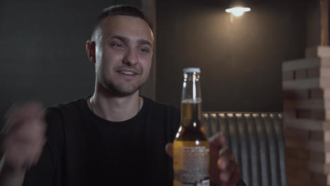 Young man opening beer bottle playing wood tower in the room. Leisure indoors Footage