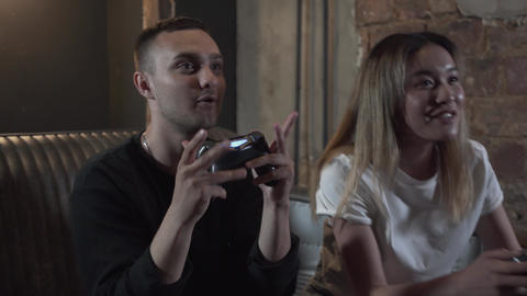 Handsome adorable young guy with his girlfrend having fun playing video games Footage