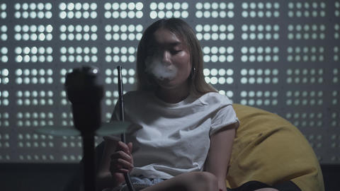 Portrait cute woman smoking hookah in the loft style room. Cute woman exhales Live Action