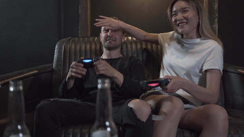 Handsome young guy with his girlfrend having fun playing video games drinking Footage