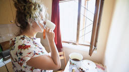 Young woman standing in rustic countryside kitchen drinking tea or coffee Footage