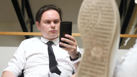 Young Man Using Smartphone at Workplace Live Action