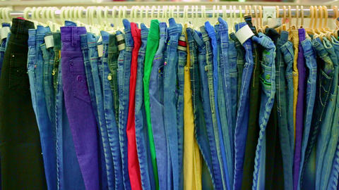 Interior of dress store. Jeans hanging on hangers on the rack in the clothing store Live Action