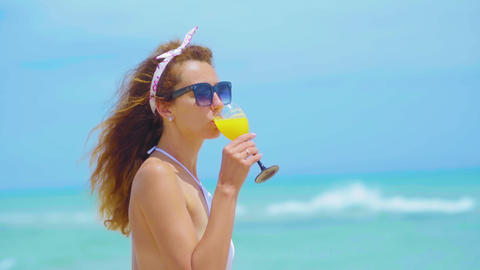 Portrait of the young cheerful attractive girl, drinking orange juice and Footage