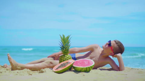 smiling boy lies on the seashore with a composition of exotic fruits against the Footage