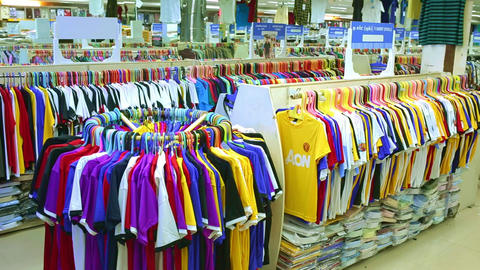 Interior of kids store. Racks with kids clothes display wall shelves in children's clothing store Footage