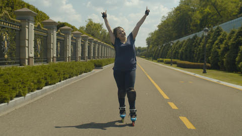 Joyful female rollerskating at speed on park path Footage