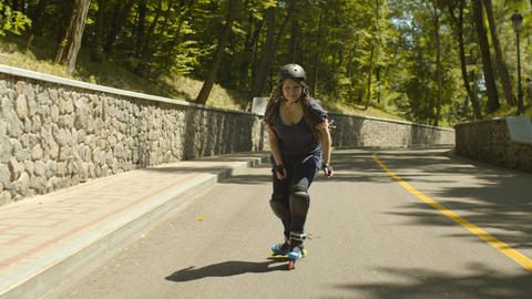 Happy woman riding roller skates at speed downhill Footage