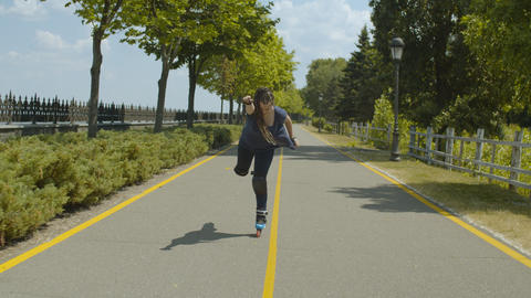 Cheerful woman roller having fun skating in park Footage