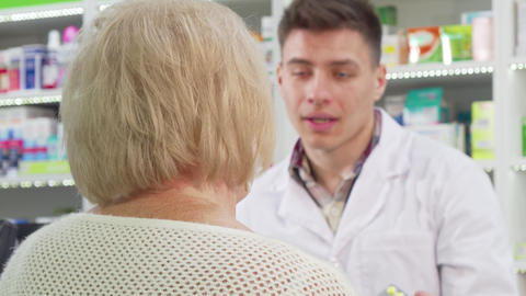 Rear view shot of a senior woman smiling to the camera after buying medicine Footage