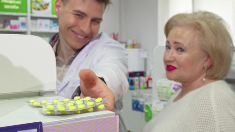Cheerful pharmacist offering elderly female customer medication in pills Footage