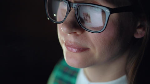 Woman in glasses looking on the monitor and surfing Internet. The monitor screen Live Action