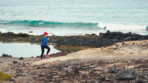 Woman runs along the stony shore of the ocean. Healthy active lifestyle Footage