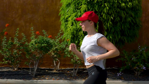 Woman runs down the street among the palm trees. Healthy active lifestyle. Slow Footage