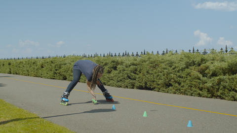 Female roller picking up cones after ride outdoors Footage