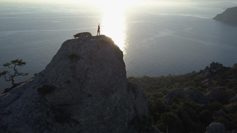 Aerial silhouette of young woman on the top of a mountain in beautiful scenery Footage