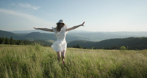 Girl running on the mountain valley. Happy woman having fun running in field Live Action