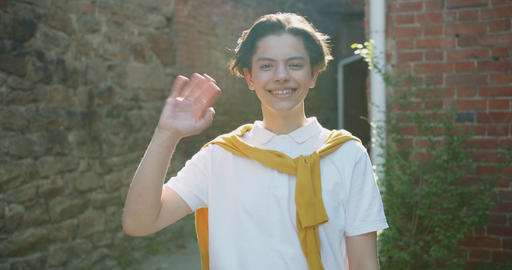 Portrait of friendly young boy waving hand and smiling standing outdoors Footage