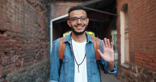 Portrait of friendly cheerful Arabian man waving hand outdoors smiling Footage