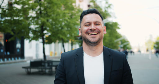 Portrait of joyful middle-aged man laughing looking at camera outdoors in city Footage
