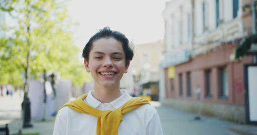 Portrait of cheerful boy teenager smiling looking at camera outside in street Footage