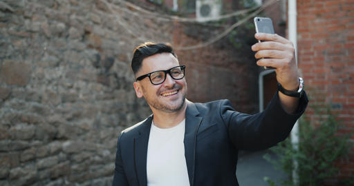 Joyful middle-aged man taking selfie with smartphone camera outdoors smiling Footage