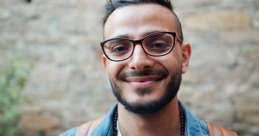 Close-up portrait of good-looking Arabian man in glasses standing outdoors Footage