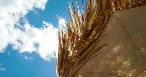 straw beach umbrella under blue sky, movement on wind, summer holiday Footage