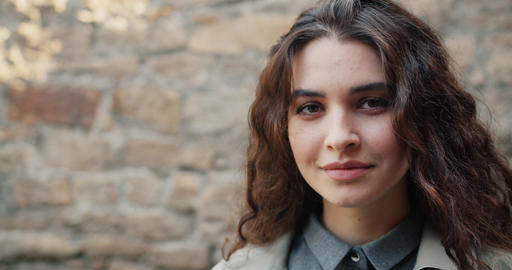 Close-up portrait of charming girl looking at camera smiling standing outdoors Footage