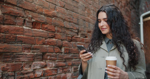 Happy woman using smartphone touching screen and smiling walking outdoors Footage