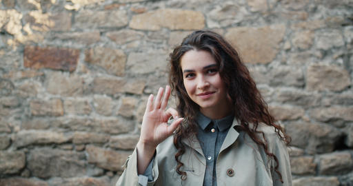 Portrait of beautiful girl student showing OK hand gesture standing outdoors Footage