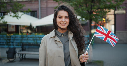 Portrait of happy girl standing outdoors with British flag smiling on windy day Footage
