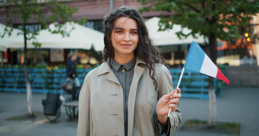 Portrait of attractive female student standing outside with French national flag Footage