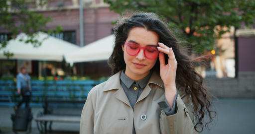 Portrait of charming young lady taking off sunglasses and smiling outdoors Footage