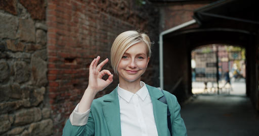 Slow motion portrait of attractive student showing OK gesture smiling outside Footage