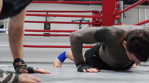 Fighters make push ups with claps on the floor on training on ringside Footage