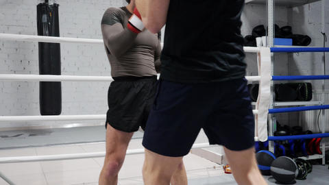 Unrecognizable boxers kick each other on the legs training on ringside in club Footage