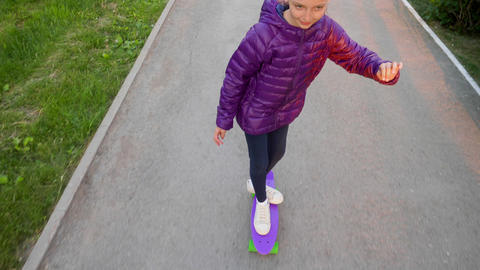 Happy child girl in jacket is rolling on purple skateboard on street in park Footage