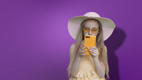 Pre-teen girl in summer hat reads phone on lilac wall background, alpha channel Footage