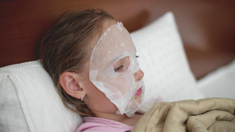 Pre-teen girl with cloth moisturizing face mask on the face laying in bed Footage