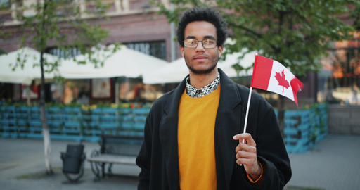 Slow motion portrait of bearded African American man outdoors with Canadian flag Footage