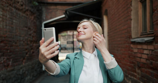 Slow motion of pretty blonde taking selfie with smartphone camera outdoors Footage
