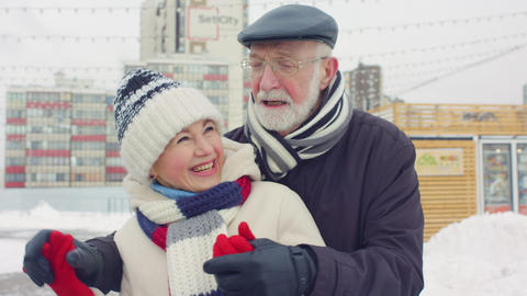 mature couple hugs having fun in park on frosty grey day Footage
