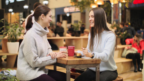 pretty ladies talk in cozy restaurant at shopping mall Footage