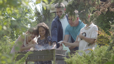 Happy friendly family making bbq in the garden close-up. Summertime leisure Live Action