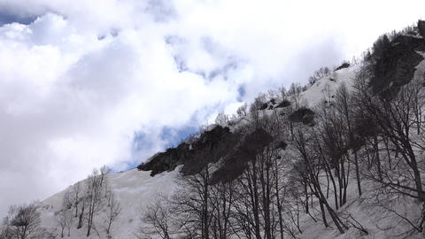 Bright cumulus clouds over dull snowy mountain slope, aerial view in motion Footage