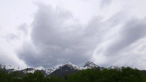 Gray clouds fly towards over rocky mounts, time lapse shot, low angle view Footage