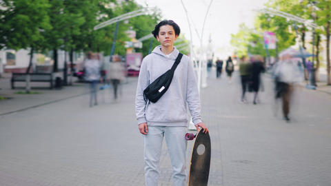 Zoom-out time lapse of young skateboarder standing outdoors in street with board Footage