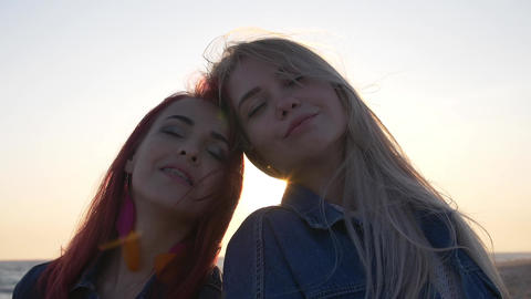girlfriends smiling in the background of the sunset the wind stirs their hair Live Action